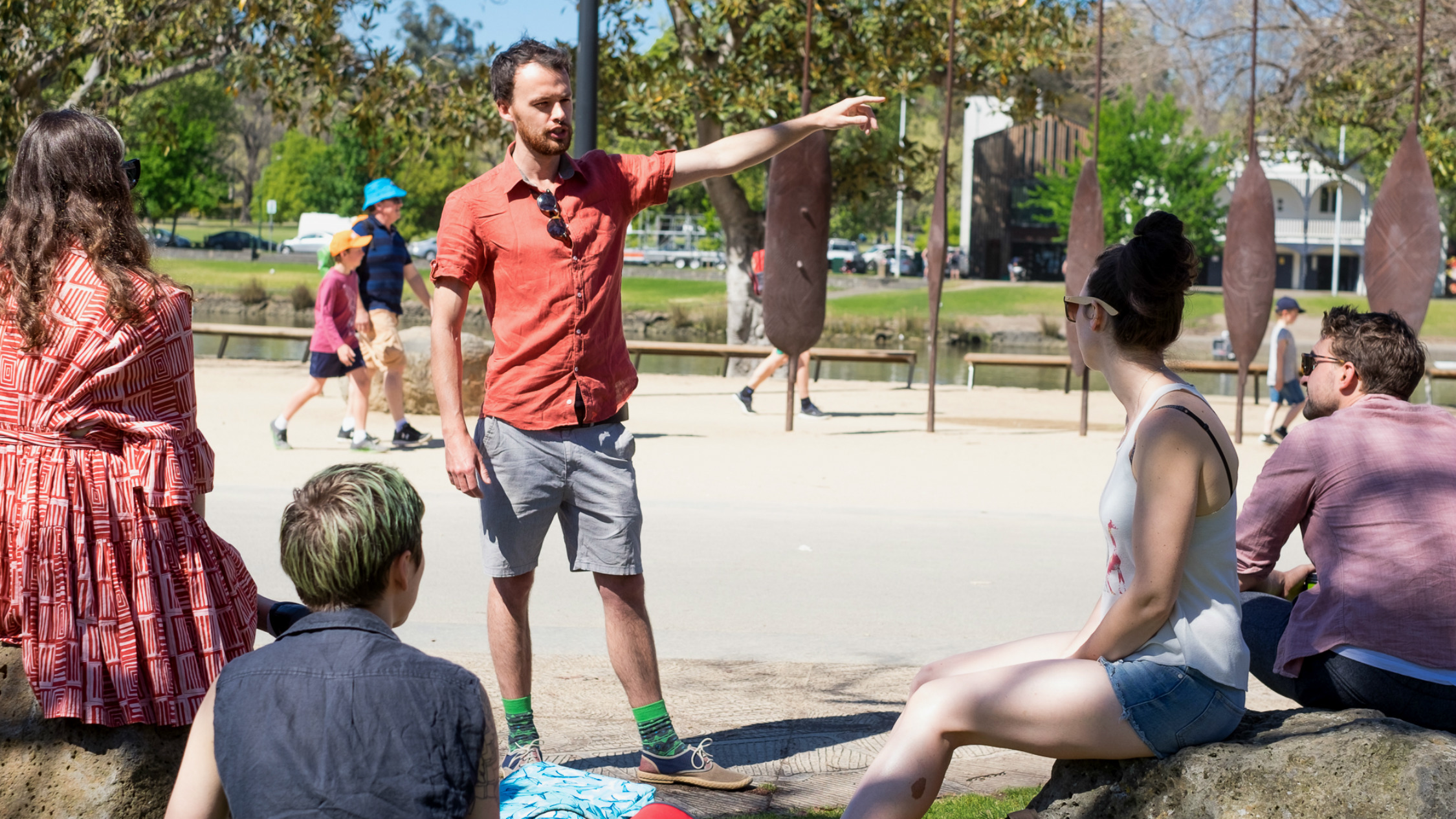A man in a t-shirt and shorts talking to people at Birrarung Marr