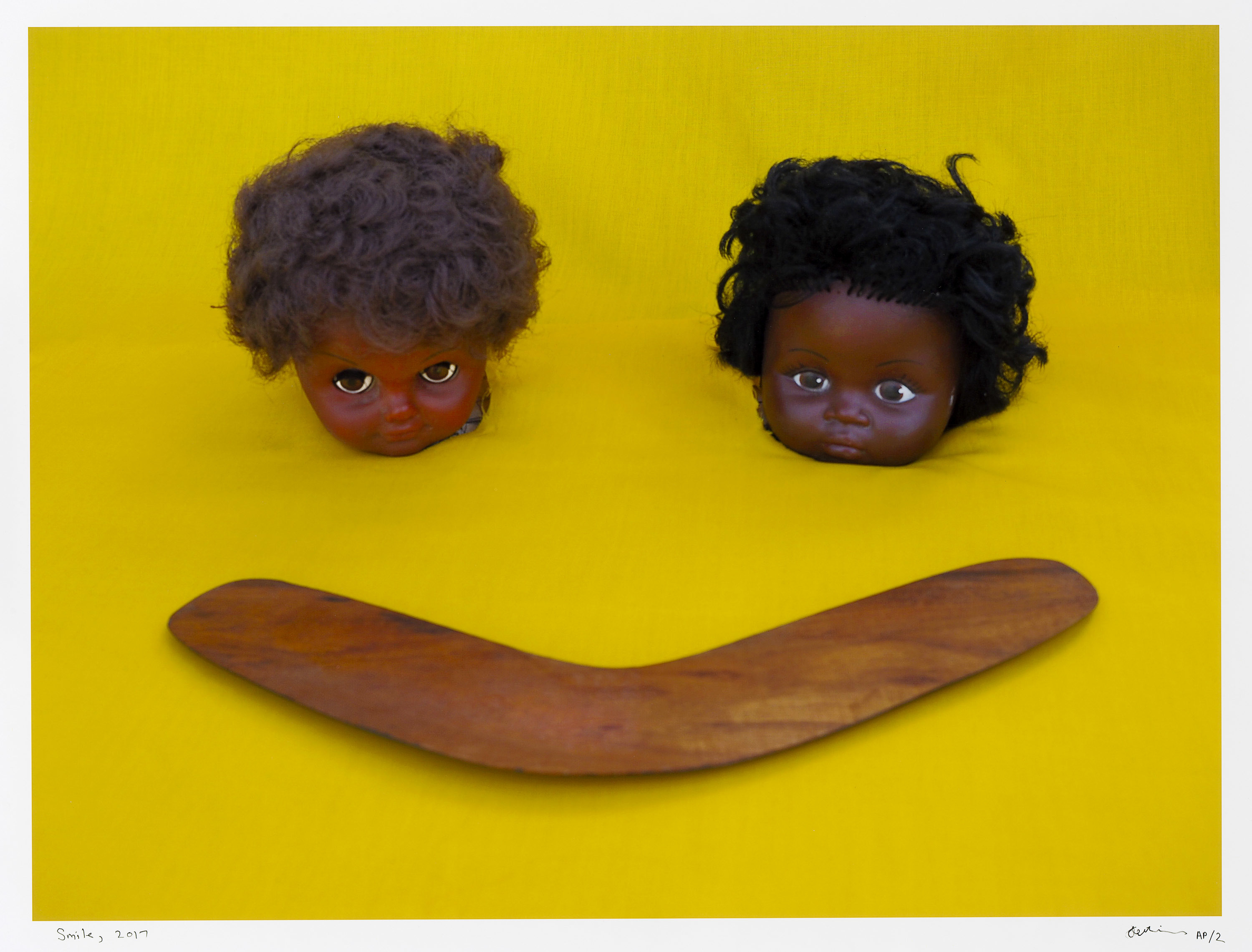 Two doll heads on a yellow backdrop with a wooden boomerang in front of them