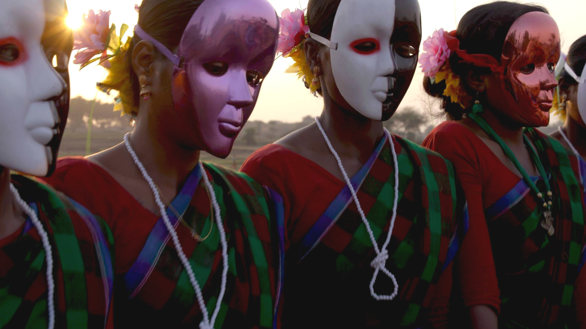 A film still featuring women wearing saris with full-face drama masks over their faces