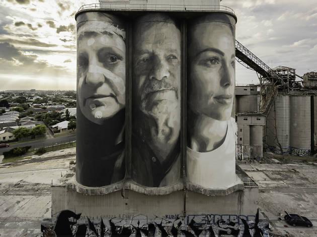 Three monochromatic faces painted on three silos
