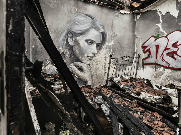 A mural of a woman thinking in an abandoned building