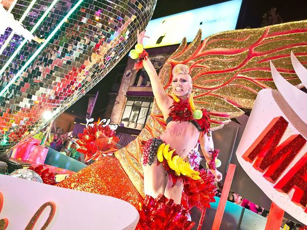 A drag queen wearing bananas dances on a glittery float.