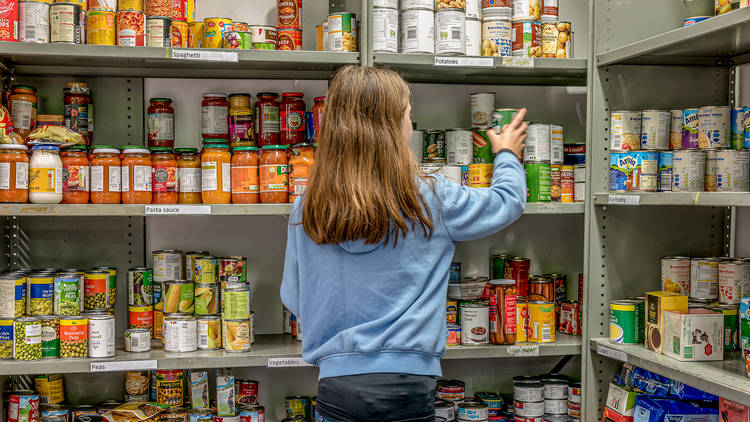 Person stacking shelves with cans