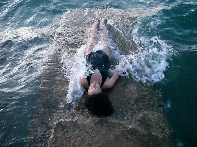 An image of a woman in a black bathing suit lying on a concrete block being covered by ocean waves.