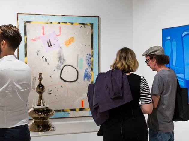 People peruse paintings in a gallery.