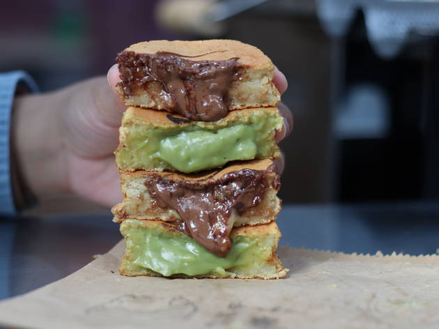 Two wheelcakes cut in half and stacked on top of each other as someone holds them up, with the custard oozing out of them