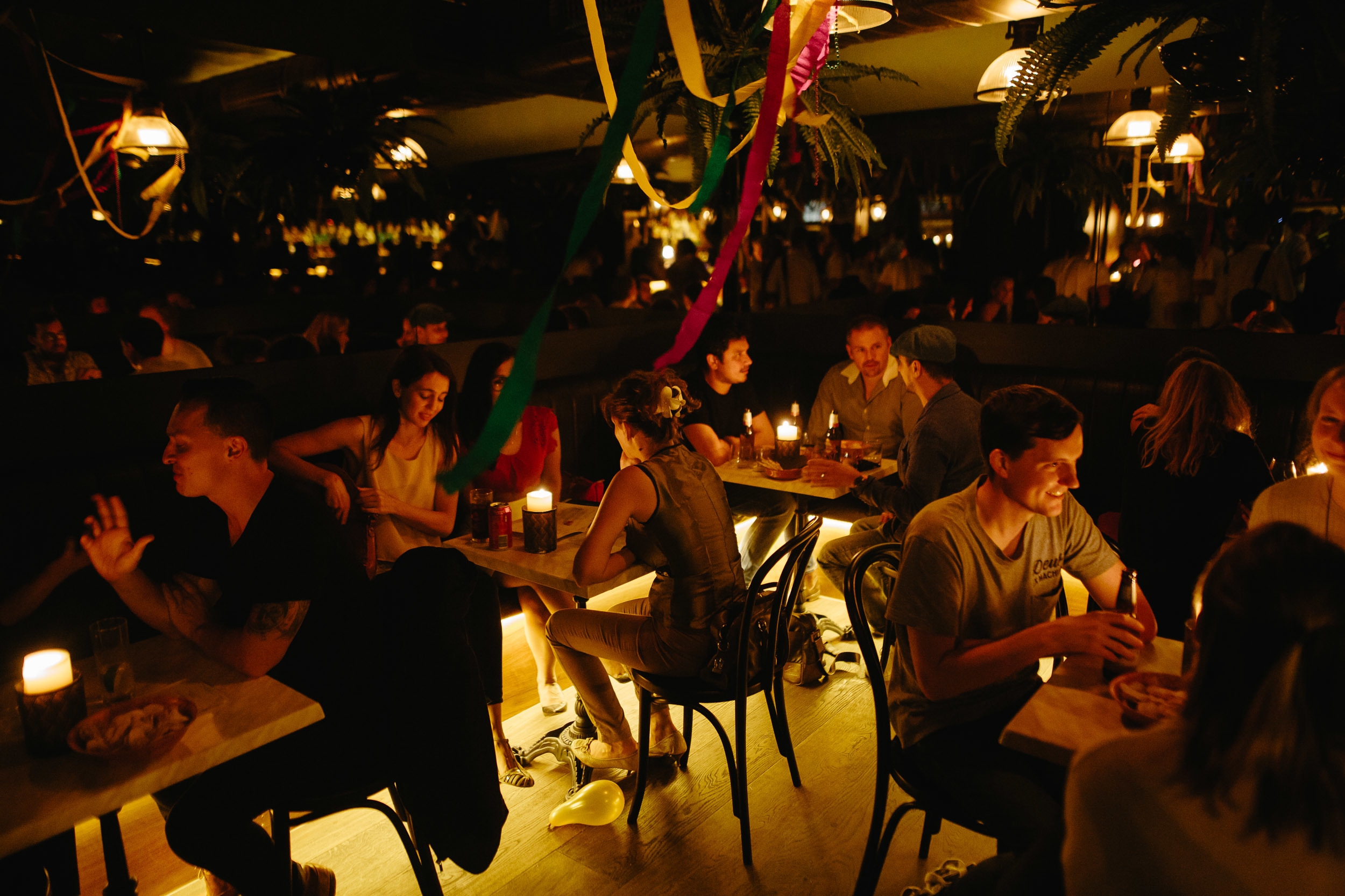 People sitting at tables inside the dimly lit Swinging Cat