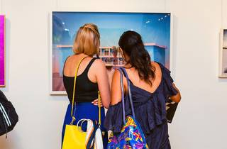 Two people with their backs turned to the camera are looking at an artwork.
