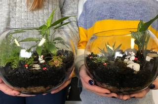 Two terrariums in glass bowls are being held up by people wearing jumpers.