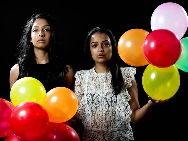 Two women with blank expressions stand holding colourful balloons.
