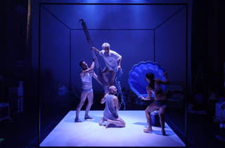 People in white dancewear performing under a blue light