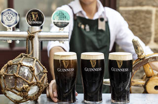 Three pints of Guinness on the bar at the Doss House