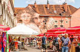 Springtime sales at Zagreb's Dolac marketplace overlooked by street art