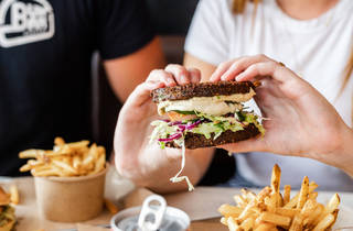 Two hands holding a burger with falafel buns