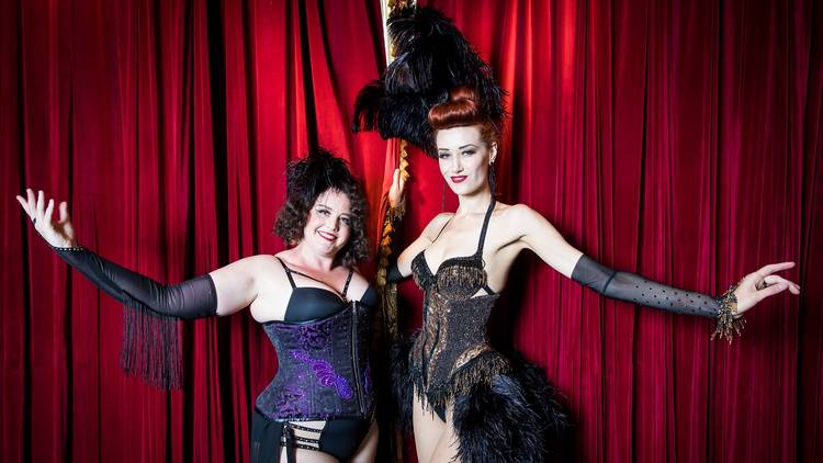 Two feminine presenting performers wearing corsets and black feathers pose in front of a red curtain.