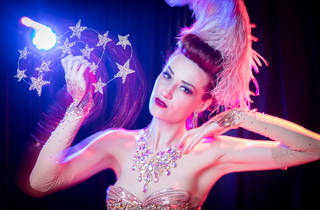 Porcelain Alice wears soft pink glittering outfit and accessories, she is twirling a crown of stars and staring into the camera.