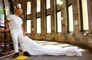 Man holding a white sheet in front of windows