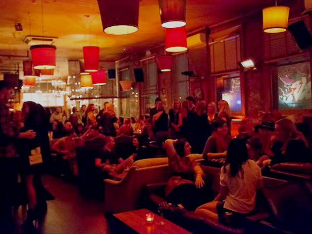 A room packed with people sitting and mingling with drinks