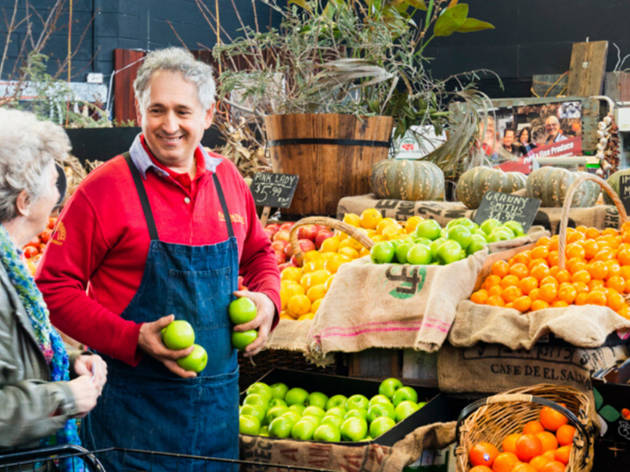 A market trader wearing an apron stands in front of boxes of fresh apples and oranges, talking to an elderly person