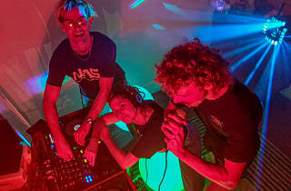 Three DJs with a mixing board and disco lights smile up at the camera.
