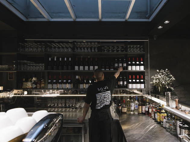 A staff member reaching for a bottle of wine from the shelf at the bar at Soul Dining in Surry Hills.