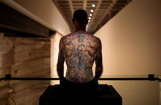 Man with a tattooed back sitting on a box