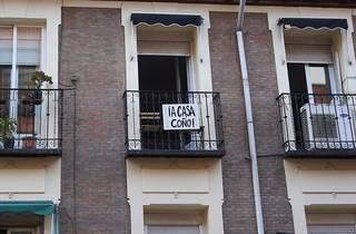Un balcón con un cartel pidiendo que la gente se queda en casa