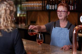 Woman wearing apron standing behind the bar pouring a glass of rose wine for a person