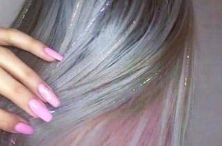 Mujer con extensiones de glitter y uñas rosa