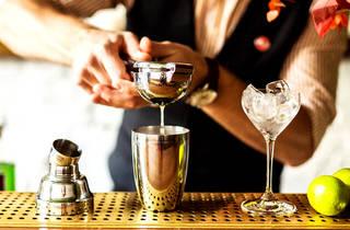 Un bartender preparando un cóctel