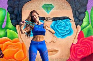 Mujer haciendo deporte frente a un mural de Frida Kahlo