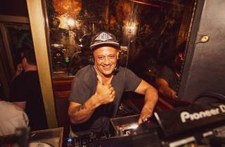 A DJ giving a thumbs up from behind the decks
