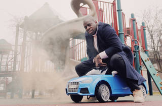 Chicago musician NNAMDI on a toy car in a park