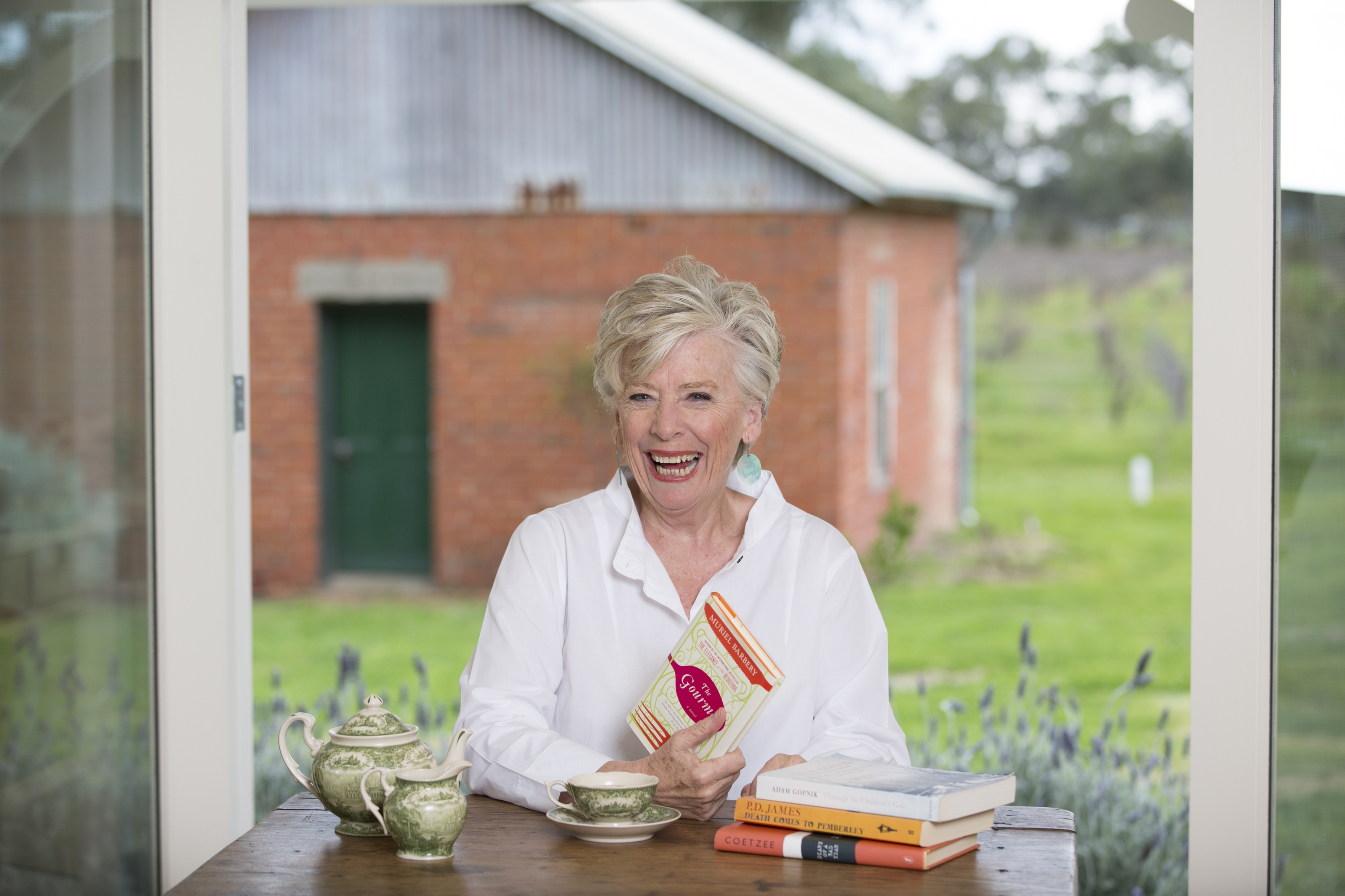 Maggie Beer sitting at a table holding one of her cookbooks.