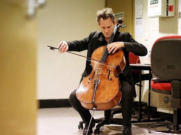 Man playing cello on a desk chair