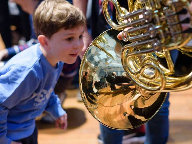 Small boy peering into a French horn