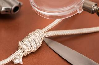 A close up shot on a red surface shows a noose, a knife, a gun and a looking glass.