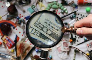 A magnifying glass is held over a table covered in miscellaneous objects.
