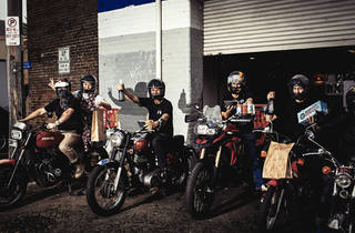 The staff at Rising Sun Workshop on motorcycles delivering food