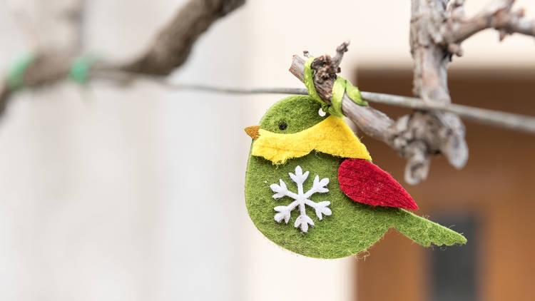 Small green handicraft bird hanging on a wire