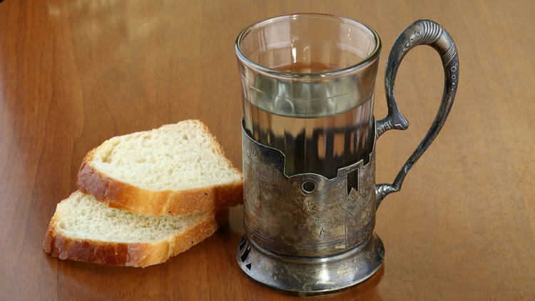 Faceted glass of hot water for tea in an ancient silver cup holder and two slices of bread