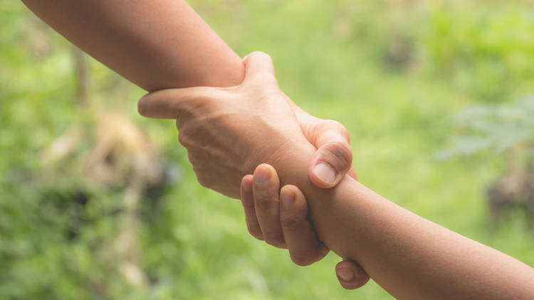 Two pairs of hand touch together, helping hands concept. Helping