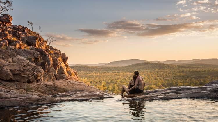 Couple sitting at Gunlom Falls, Kakadu