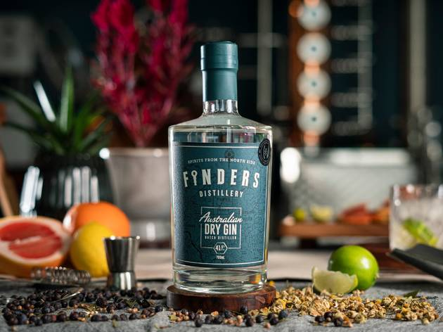 A bottle of Finders dry gin with fresh fruit and botanicals in the background.
