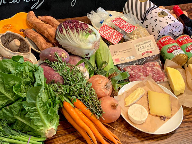 An unpacked box of fresh produce and pantry staples on a table at Dear Sainte Eloise