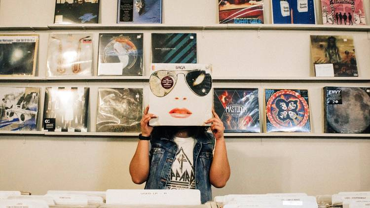 Woman holding vinyl record to her face