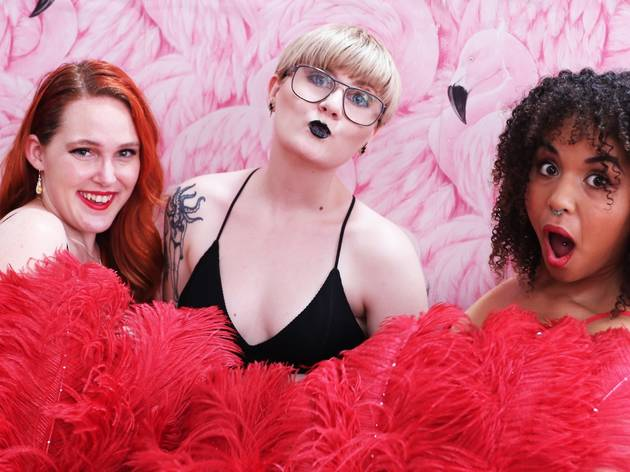 Three people pose against a pink flamingo wallpaper, they are holding red feather fans in front of them and wearing lingire.