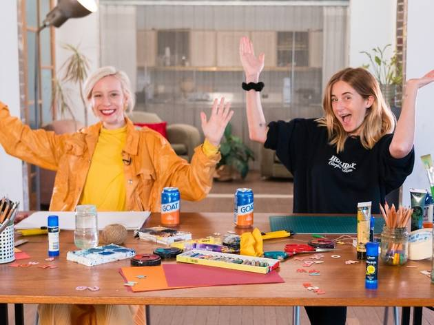 Two people sit at a table covered in craft supplies with tins of beer, their hands are in the air, they look excited.