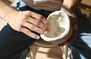 Man carves a bowl out of clay