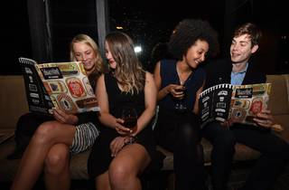 Four people reading Time Out magazines